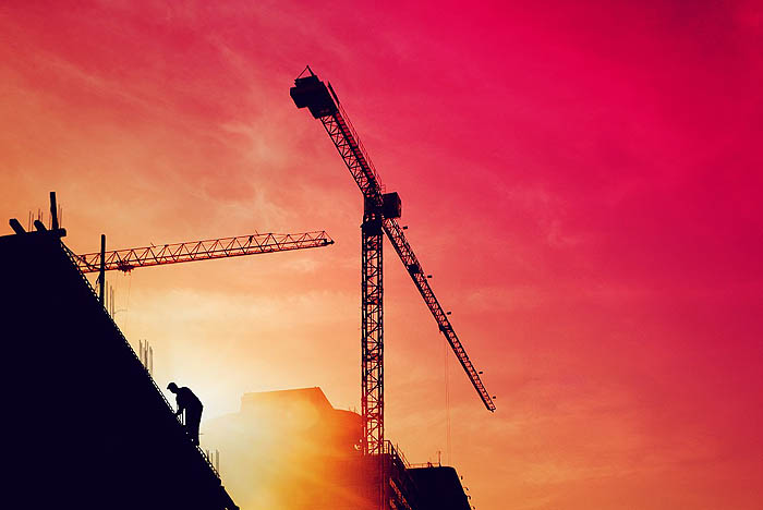 Construction worker on a building in sunset